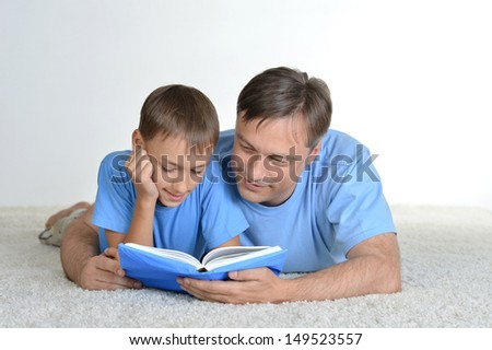 Dad and son reading a book on the floor - stock photo