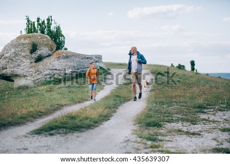 Dad and son running on the field with the dog - stock photo