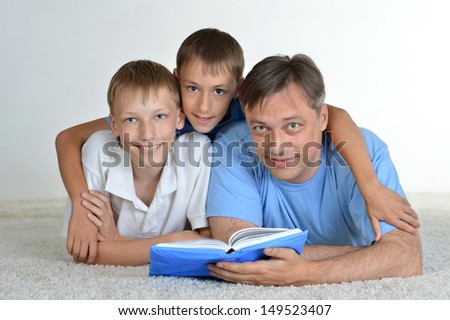 Dad and sons reading a book on the floor - stock photo