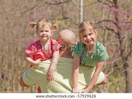 Dad Carrying His Daughters - stock photo