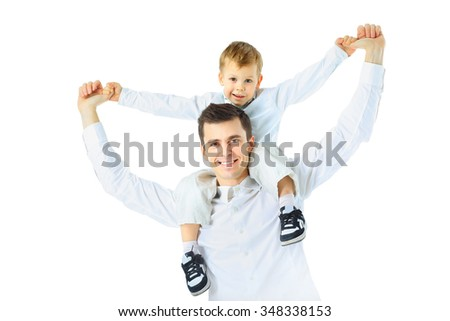 Dad holding his son on his shoulders, his arms outstretched - stock photo