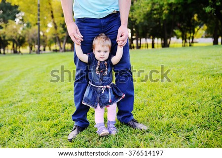Dad holds baby daughter's hands on the background of trees. Dad and daughter relaxing in the park grass ene - stock photo