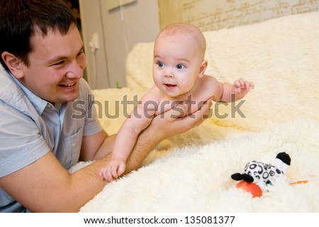 Dad keeps his little daughter in his arms - stock photo