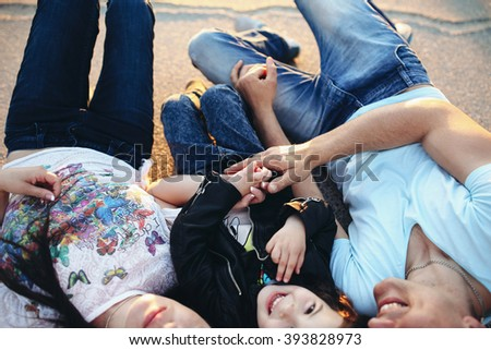 Dad mom and child actively spend time in the park - stock photo