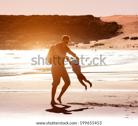 Dad playing with baby daughter on the beach at sunset - stock photo