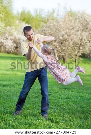 Dad playing with his baby daughter in a pink dress, he turns her around himself at arm's length, selective focus, the effect of motion - stock photo