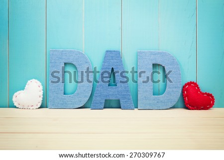 DAD text letters with white and red hearts over blue wooden background - stock photo