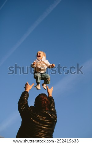 Dad throws a happy daughter against the blue sky - stock photo