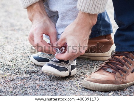 Dad tying the laces on a child sneakers - stock photo