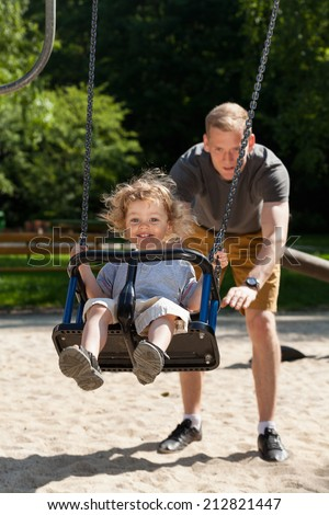 Dad with child on the playground, vertical - stock photo