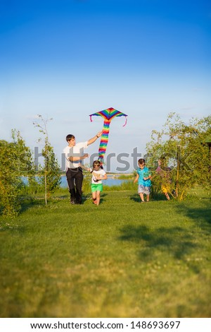Dad with kids running with kite outdoors - stock photo