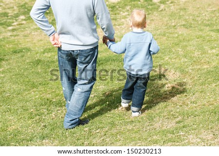 Dad with little boy outdoors at park - stock photo