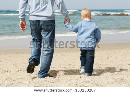 Dad with little boy outdoors at sea  - stock photo