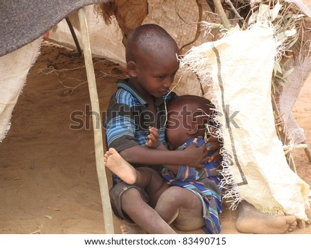 DADAAB, SOMALIA-AUGUST 15: An unidentified comforts an unidentified toddler in a tent in the Dadaab refugee camp where thousands of Somalis wait for help because of hunger on August 15, 2011 in Dadaab, Somalia. - stock photo