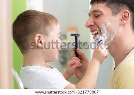 Daddy and his child son shaving and having fun in bathroom - stock photo