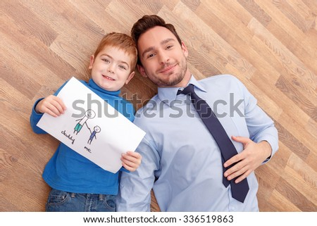 Daddy and me. Cheerful young man and his son are laying on flooring together. They are looking at camera and smiling. The boy is showing the picture of his family - stock photo