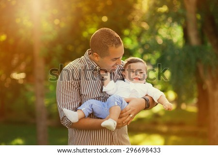 Daddy playing with his son outside. Happy family portrait.  Laughing Dad with little boy enjoying nature together. Joyful family. - stock photo