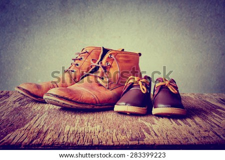 Daddy's boots and baby's shoes, fathers day concept.  - stock photo
