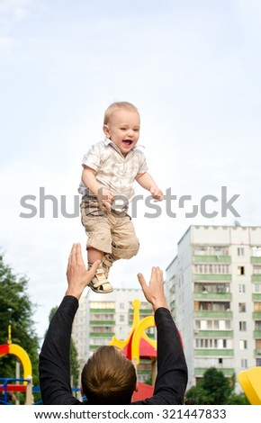 daddy tossing his infant son up on sky background in city outdoors - stock photo