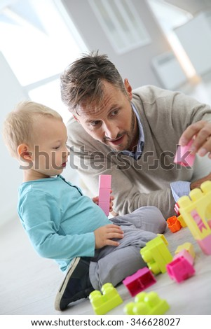 Daddy with baby boy playing with blocks on the floor - stock photo