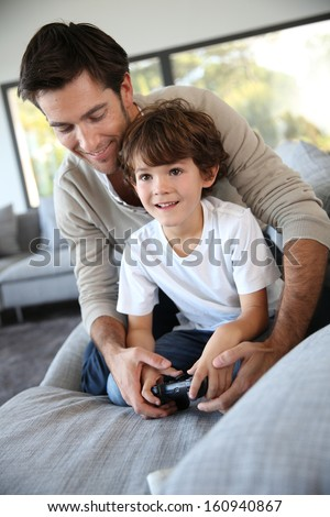 Daddy with kid playing video game - stock photo