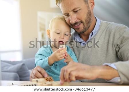 Daddy with 2-year-old boy playing with wooden blocks - stock photo