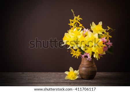 Daffodil in vase on brown background - stock photo