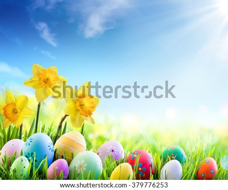 Daffodils And Colorful Decorated Eggs On Sunny Meadow - Easter Holiday Background  - stock photo
