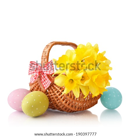 Daffodils in wicker basket with easter eggs isolated on white background - stock photo