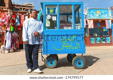 DAHAB, EGYPT - JANUARY 29, 2011: Vendor on the street next to stand. Street food is the cheapest way for tourists to get a meal. - stock photo
