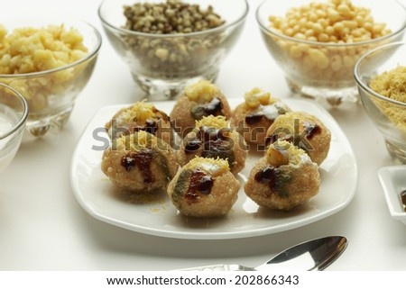 Dahi Batata Puri - indian chaat snack made with tangy sauce fried bread vegetables curd potato and sev. - stock photo