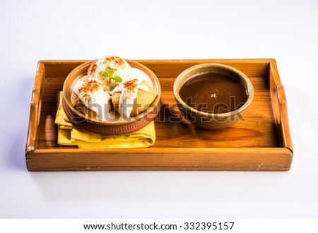 dahi vada or dahi bhalla, indian snacks, served with tamarind chutney, top view on white background - stock photo