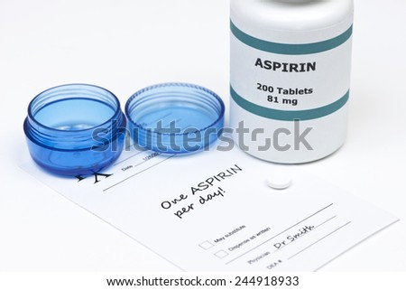 Daily aspirin tablet with aspirin bottle, container, and prescription. - stock photo