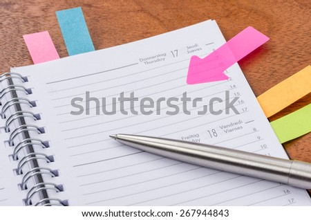 Daily planner with some sticky notes - stock photo