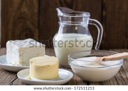 Dairy milk products: cheese, milk,  sour cream,  butter on rustic wooden background - stock photo