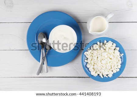 Dairy products: cottage cheese, milk and sour cream in blue dishware on white wooden table. Top view point. - stock photo
