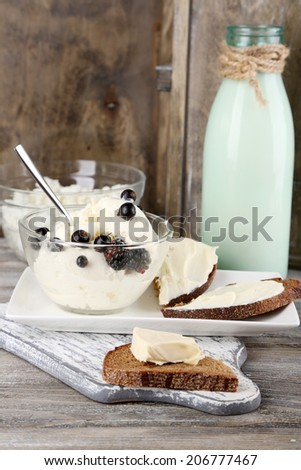 Dairy products: milk, butter, cottage cheese on wooden background - stock photo