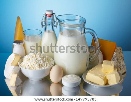 Dairy products, milk, cheese, egg, yogurt, sour cream, cottage cheese and butter on blue background still life - stock photo