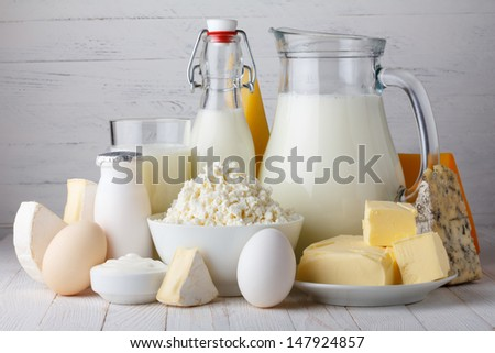 Dairy products, milk, cottage cheese, eggs, yogurt, sour cream and butter on wooden table - stock photo