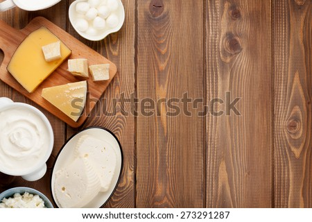 Dairy products on wooden table. Sour cream, milk, cheese, yogurt and butter. Top view with copy space - stock photo