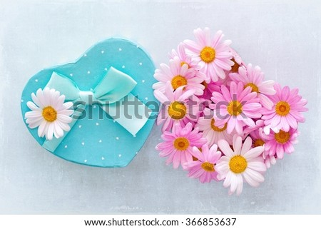 Daisy flowers and a box with a gift on a blue background with texture . - stock photo