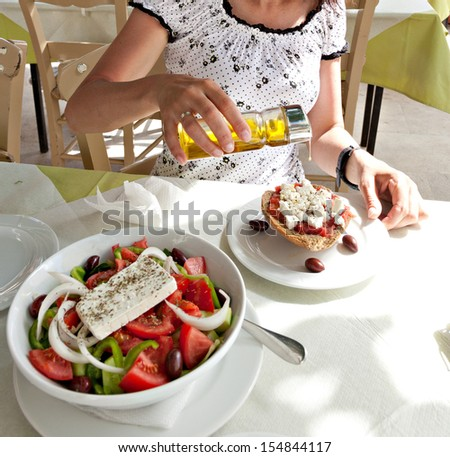 Dakos - traditional Cretan food.  A slice of roasted barley bread with cheese, olives, tomato and olive oil.  - stock photo