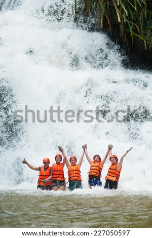 DALAT, VIETNAM - JULY 28, 2014: Unidentified Caucasian young women tourists having abseiled in Datanla waterfall pose for camera smiling happily with arms spread. - stock photo
