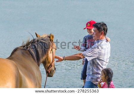 DALAT, VIETNAM - JUNE 8, 2014: An unidentified man holding his son pats a horse at Xuan Huong Lake. This artificial lake in the city centre is a favourite place for tourists and locals for walking. - stock photo