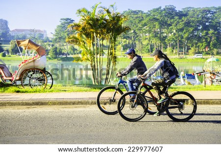 DALAT, VIETNAM - SEP 25: man and women riding a bicycle on road at Xuan Hng lake, Da Lat, Vietnam. On Sep 25, 2014. Da lat is one of the best tourism city in Vietnam. - stock photo