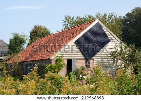 DALFSEN, THE NETHERLANDS - SEPTEMBER 16, 2014: Modern farming in Holland;  a solar panel on a Dutch barn in Dalfsen, Overijssel, The Netherlands on Sept. 16, 2014. - stock photo