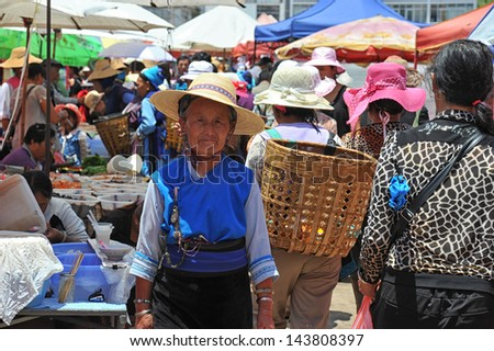 DALI, CHINA - JUNE 15: Chinese farmers sell their goods on the market on June 15, 2013 in Dali, China. Many farmers depend on selling their products here and only make around $800 a year. - stock photo
