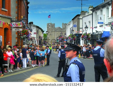 DALKEY, IRELAND - JUNE 18: Unidentified people and police officers await the arrival of Michelle Obama on June 18, 2013 in Dalkey, Ireland. - stock photo