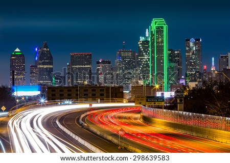 Dallas skyline by night The rush hour traffic leaves light trails on I-30 (Tom Landry) freeway. - stock photo