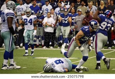 DALLAS, TEXAS - DEC 14: Dallas Cowboys Quarterback Tony Romo is sacked by the NY Giants defense during a game at Texas Stadium  in Dallas, Texas, on Sunday, December 14, 2008. - stock photo